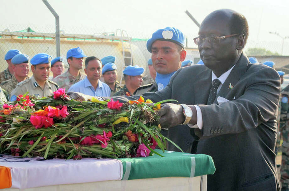 In this photo released by the United Nations Mission in South Sudan (UNMISS), South Sudan's Minister of Foreign Affairs and International Cooperation Dr. Barnaba Marial Benjamin lays flowers on the coffins of the two Indian peacekeepers who were killed on Thursday, at a memorial service held in the UNMISS compound in Juba, South Sudan, Saturday, Dec. 21, 2013. The U.N. peacekeeping mission strongly condemned the unprovoked attack on a U.N. base in Akobo in Jonglei state, near the Ethiopian border, on Thursday that killed two Indian peacekeepers, injured a third, and also killed at least 11 civilians who had sought refuge there. (AP Photo/UNMISS) / UNMISS