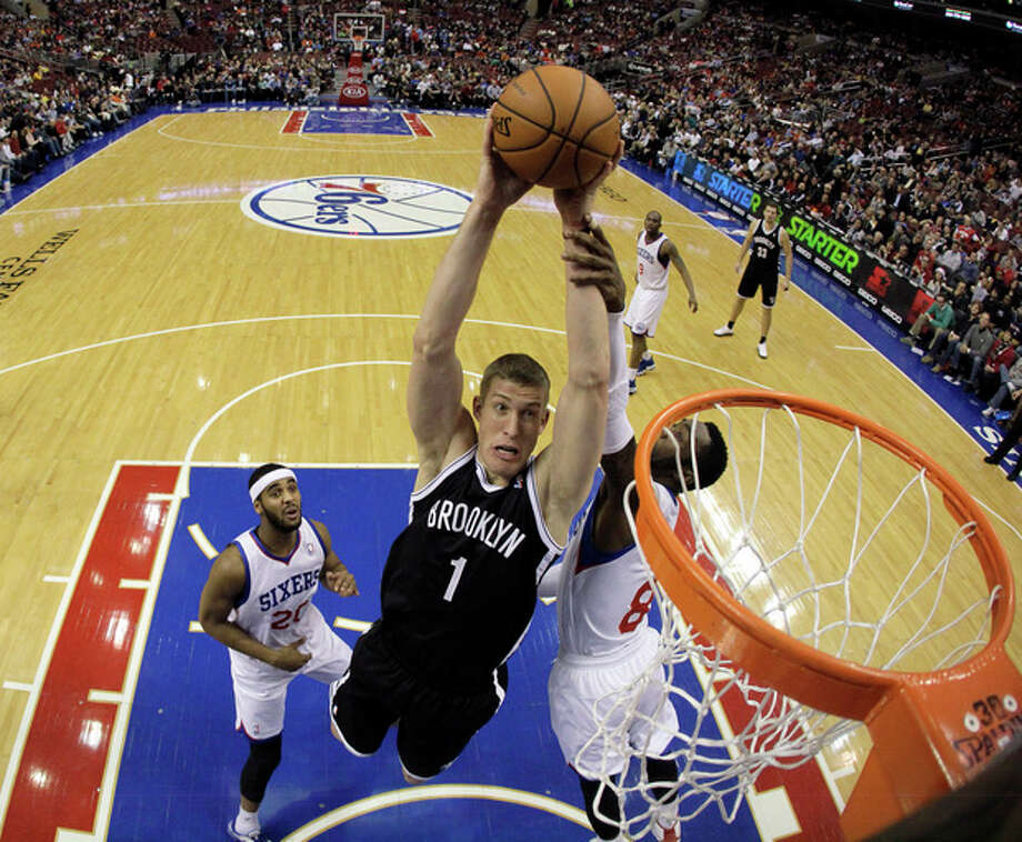 Brooklyn Nets' Mason Plumlee (1) goes up for a shot against Philadelphia 76ers' Brandon Davies (20) and Tony Wroten (8) during the first half of an NBA basketball game, Friday, Dec. 20, 2013, in Philadelphia. (AP Photo/Matt Slocum) / AP