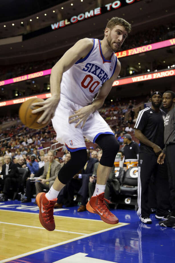 Philadelphia 76ers' Spencer Hawes chases the loose ball out of bounds during the first half of an NBA basketball game against the Brooklyn Nets, Friday, Dec. 20, 2013, in Philadelphia. (AP Photo/Matt Slocum)