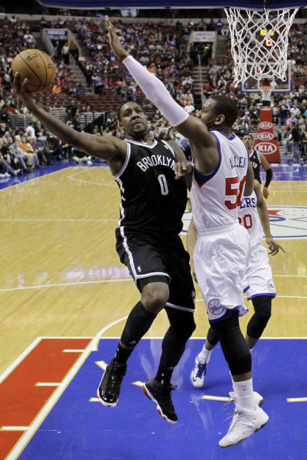 Brooklyn Nets' Andray Blatche (0) goes up for a shot as Philadelphia 76ers' Lavoy Allen (50) defends during the first half of an NBA basketball game, Friday, Dec. 20, 2013, in Philadelphia. (AP Photo/Matt Slocum)