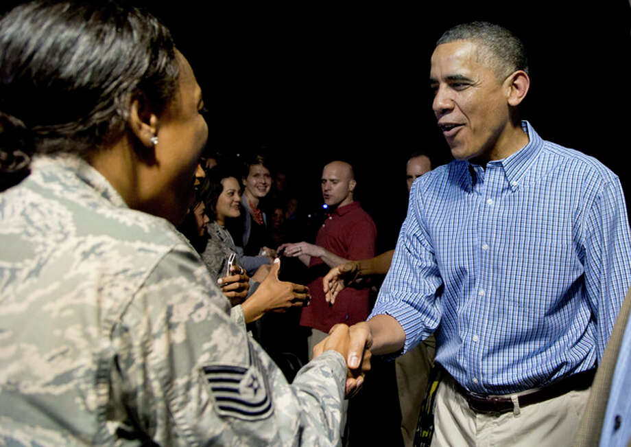 President Barack Obama, right, greets members of the military as he arrives with the first family on Air Force One at Joint Base Pearl Harbor-Hickam, in Honolulu, Friday, Dec. 20, 2013. The first family will be spending their annual winter vacation in Hawaii and return to Washington on Jan. 5, 2014. (AP Photo/Carolyn Kaster) / AP