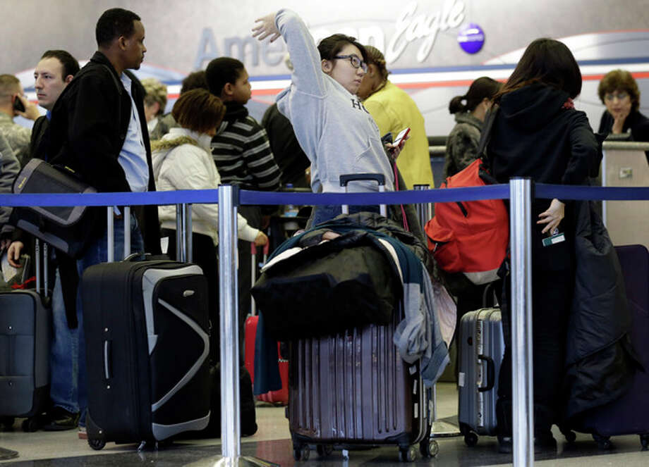 Passengers line up at ticket counters inside Terminal 3 at O'Hare International Airport in Chicago on Friday, Dec. 20, 2013. A local weather forecast predicts rain will continue Friday with some light freezing drizzle, with a chance of rain and sleet Saturday morning, turning to snow and sleet in the afternoon. A stew of foul weather, ranging from freezing rain and snow in the Midwest to thunderstorms and possible tornadoes in the South, is arriving just in time for one of the busiest travel weekends of the year. (AP Photo/Nam Y. Huh) / AP
