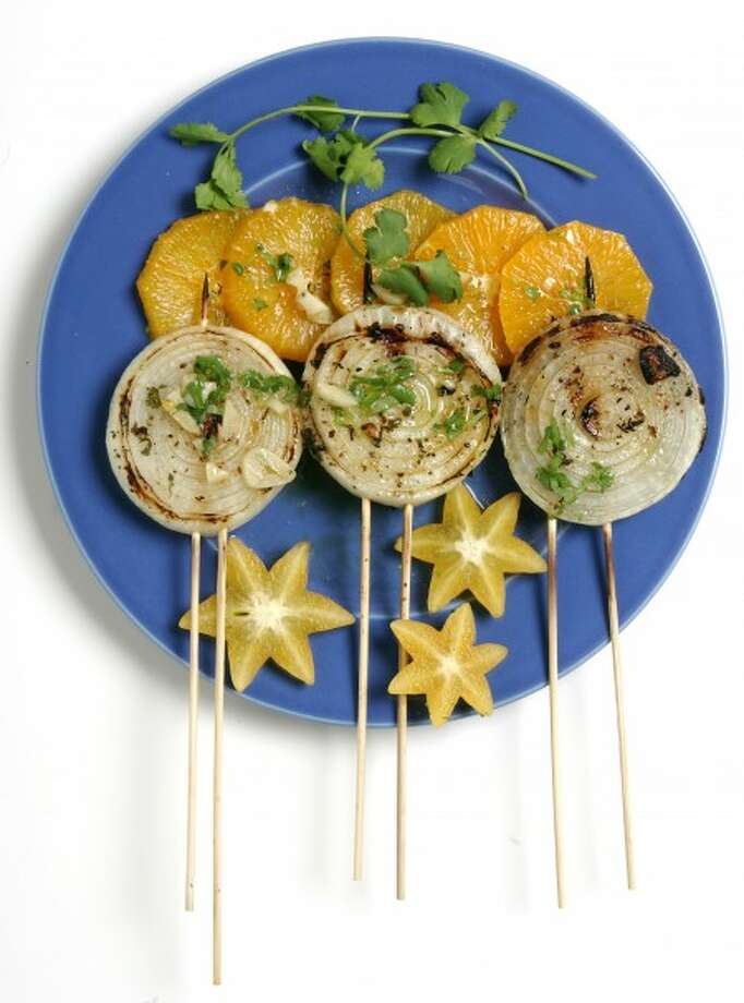 Grilled sweet onion slices topped with mojo, served with slices of orange and starfruit, uses an easy to make rub. (Nick Koon/Orange County Register/MCT)