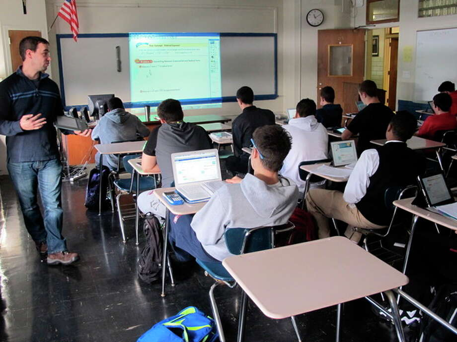 AP Photo/Jim FitzgeraldIn this Dec. 13, photo, math teacher Richard Yapchanyk, left, leads a math class at Archbishop Stepinac High School as students use tablets and laptop computers to follow a lesson in an online textbook in White Plains, N.Y. The school, joining a national trend, has dumped all its heavy and expensive printed textbooks and put the material online. / AP