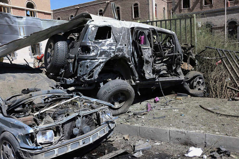 """FILE - This Thursday, Dec. 5, 2013 file photo provided by Yemen's Defense Ministry shows damaged vehicles after an explosion at the Defense Ministry complex in Sanaa, Yemen. The militant leader of al-Qaida's branch in Yemen said in a video posted on militant websites late Saturday, Dec. 21, that its fighters attacked a hospital and a place for prayer at the complex that they had been warned not to attack prior to the Dec. 5 attack. Qassim al-Rimi, commander of al-Qaida in the Arabian Peninsula later said, """"We accept full responsibility for what happened in the hospital and will pay blood money for the victims' families."""" (AP Photo/Yemen Defense Ministry, File) / Yemen's Defense Ministry"""