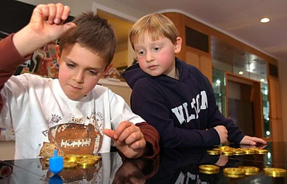 Brothers Max and Noah Levi play the dreidel game as part of their observance of Hanukkah. Hour photo / Erik Trautmann