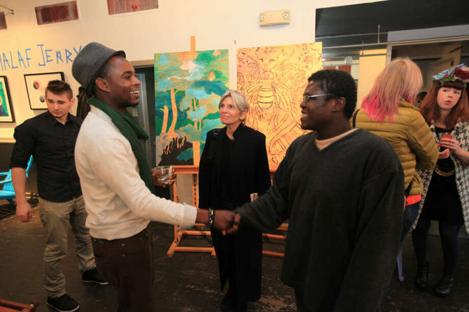 """Hour photo / Chris Palermo. Artist Khalaf Jerry greets Pierre Antoine Jr. at the """"Holiday Social Fiber Fabric Arts &Makers"""" pop up art show presented by Pop City Saturday in Norwalk."""