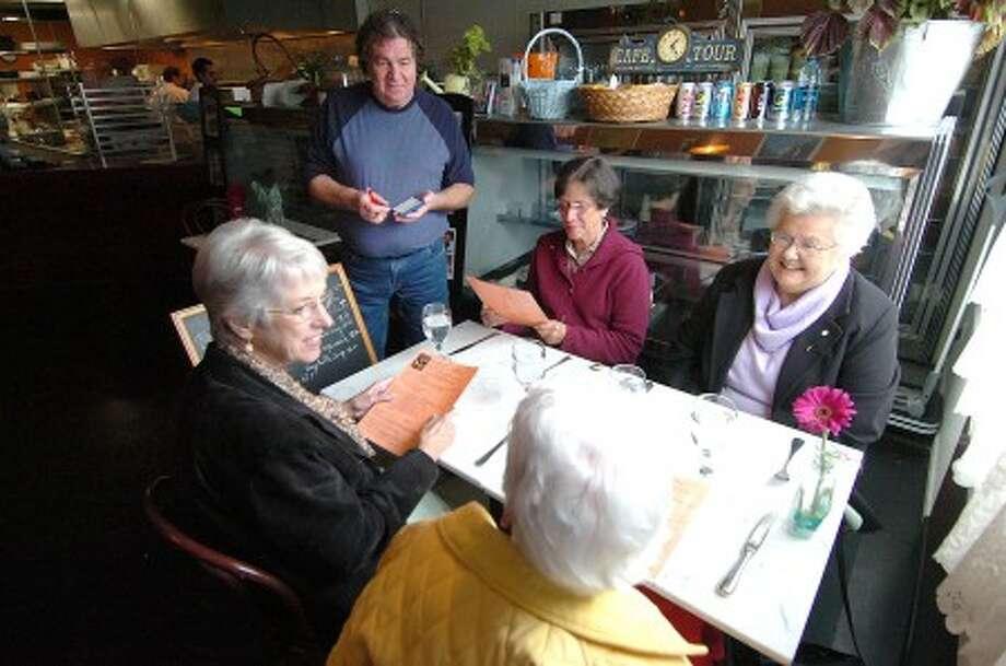 Photo/Alex von Kleydorff. Roger Martin takes some lunch orders at Bon Appetite Cafe in Wilton center.
