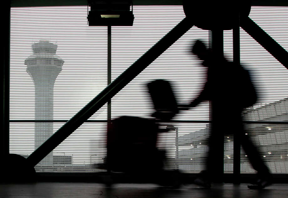 A traveler walks through Terminal 3 at O'Hare International Airport in Chicago on Saturday, Dec. 21, 2013. The National Weather Service issued a hazardous weather outlook for north central Illinois, northeast Illinois and northwest Indiana Saturday morning. (AP Photo/Nam Y. Huh) / AP