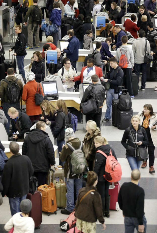 Passengers check in at Terminal 3 in O'Hare International Airport in Chicago on Saturday, Dec. 21, 2013. The National Weather Service issued a hazardous weather outlook for north central Illinois, northeast Illinois and northwest Indiana on Saturday morning. (AP Photo/Nam Y. Huh)