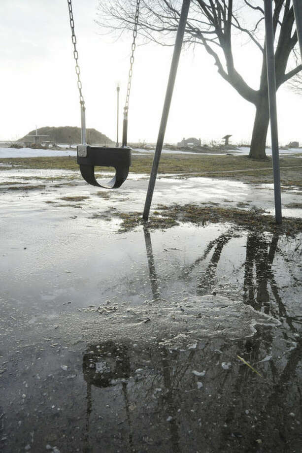 Snow melting all around the area Sunday morning leaving puddles like this at the Calf Pasture beach playground with record high temperatures. Hour photo/Matthew Vinci
