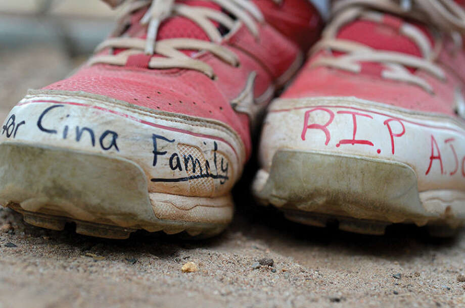 Hour Photo/Alex von Kleydorff . Message written to the family of 12 yr old Joeseph Hayes Cina who was killed on his bicycle, on the baseball shoes of player Scott Whalen during Norwalk Babe Ruth baseball