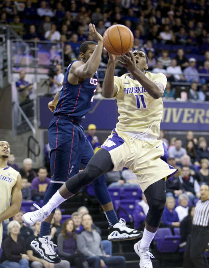 Washington's Mike Anderson, right, goes to the basket with Connecticut's Lasan Kromah defending in the first half of an NCAA college basketball game in Seattle on Sunday, Dec. 22, 2013. (AP Photo/John Froschauer)
