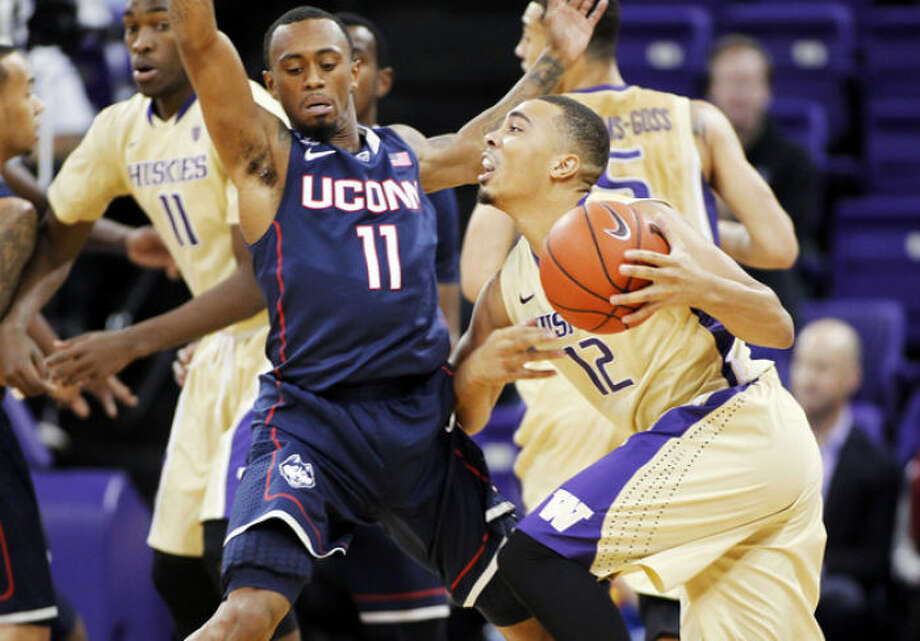 Washington's Andrew Andrews drives around Connecticut's Ryan Boatright in the first half of an NCAA college basketball game in Seattle on Sunday, Dec. 22, 2013. (AP Photo/John Froschauer)