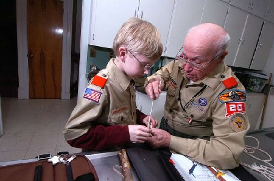 Photo/Alex von Kleydorff. Phil Antedomenico works with Boy Scout Tenderfoot Will Ruefenact on his Taut-Line Hitch and other knot tying skills at the Boy Scouts meeting at Zion Hill Church