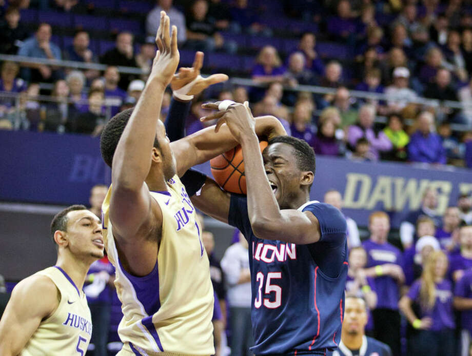 Connecticut's Amida Brimah, right, battles with Washington's Darin Johnson for a rebound with Nigel Williams-Gross behind in the first half of an NCAA college basketball game in Seattle on Sunday, Dec. 22, 2013. (AP Photo/John Froschauer) / FR74207 AP
