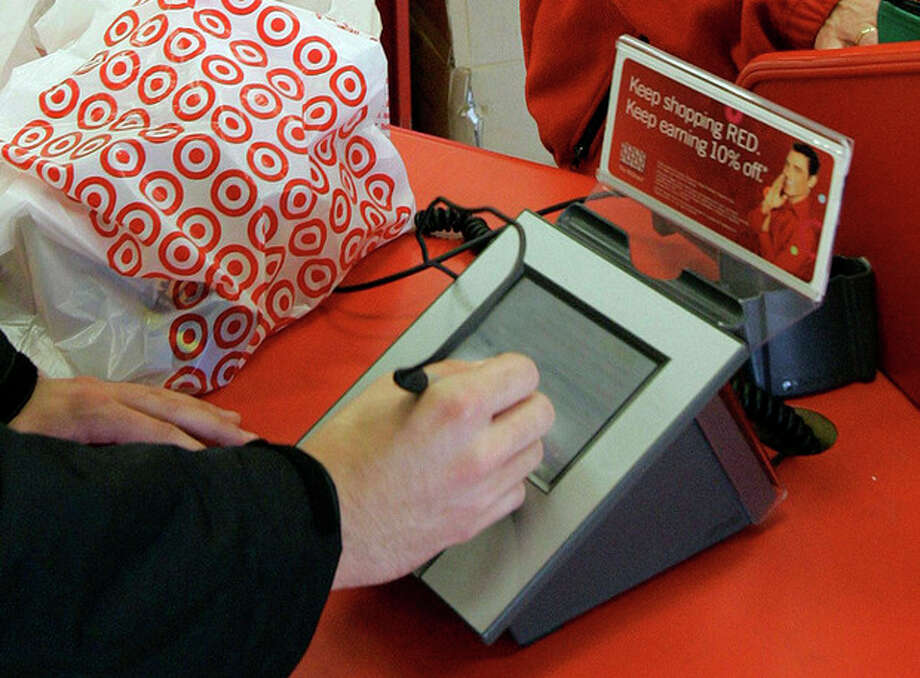 FILE - In this Jan. 18, 2008 file photo, a customer signs his credit card receipt at a Target store in Tallahassee, Fla. The U.S. is the juiciest target for hackers hunting credit card information. And experts say incidents like the recent data theft at Target's stores will get worse before they get better. That's in part because U.S. credit and debit cards rely on an easy-to-copy magnetic strip on the back of the card, which stores account information using the same technology as cassette tapes. The breach that exposed the credit card and debit card information of as many as 40 million Target customers who swiped their cards between Nov. 27 and Dec. 15 is still under investigation. (AP Photo/Phil Coale, File) / AP