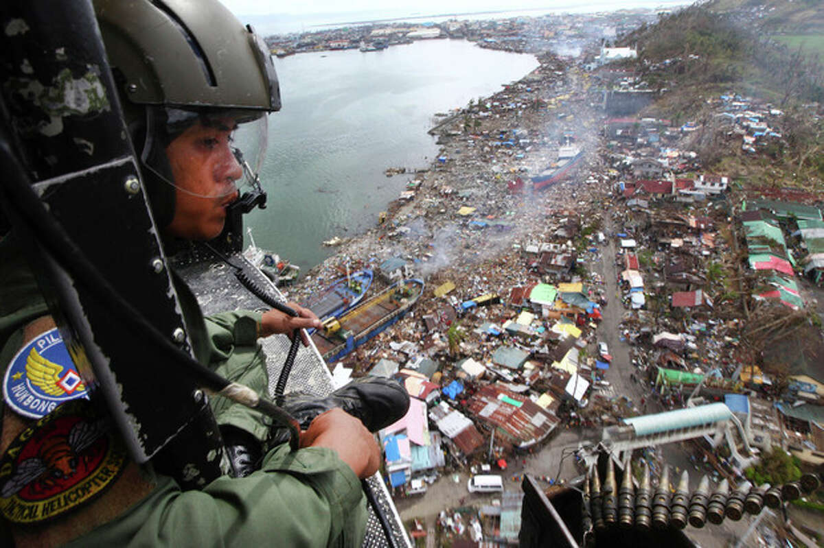 FOR USE AS DESIRED, YEAR END PHOTOS - FILE - A Philipine Air Force crew looks out from his helicopter as Typhoon Haiyan-ravaged city of Tacloban is seen in the background, during a flight to deliver relief goods in Leyte province, Philippines, Tuesday, Nov. 19, 2013. Hundreds of thousands of people were displaced by Typhoon Haiyan, which tore across several islands in the eastern Philippines on Nov. 8. (AP Photo/Dita Alangkara, File)