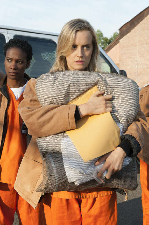 "FILE - This file image released by Netflix shows Taylor Schilling in a scene from ""Orange is the New Black."" Jennifer Lawrence edged out Miley Cyrus by one vote in The Associated Press' annual survey of its newspaper and broadcast members and subscribers for Entertainer of the Year. Netflix was a close third, earning 13 votes for altering the TV landscape with its on-demand format and hit original series ""House of Cards"" and ""Orange is the New Black."" (AP Photo/Netflix, Barbara Nitke, File)"