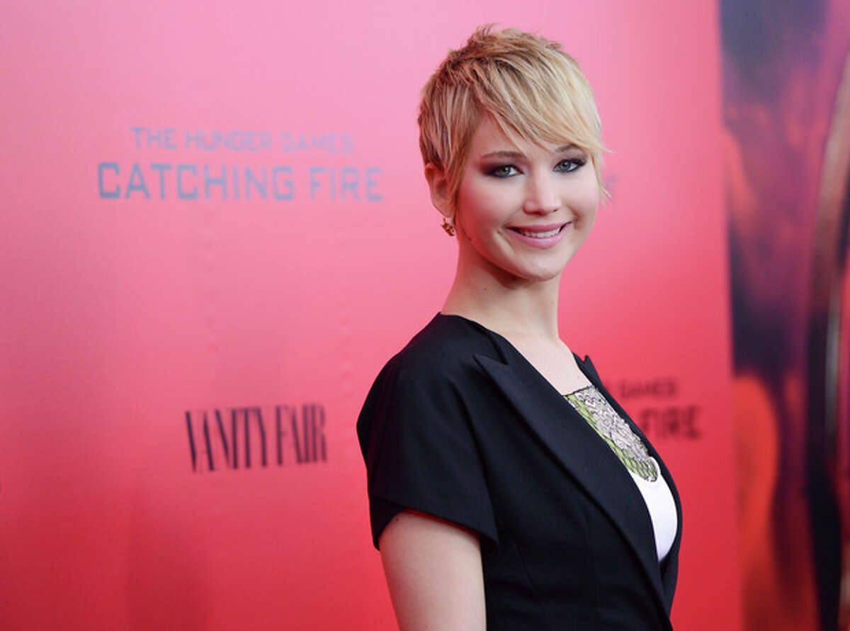 """FILE - In this Nov. 20, 2013 file photo, actress Jennifer Lawrence attends a special screening of """"The Hunger Games: Catching Fire"""" at AMC Lincoln Square in New York. Lawrence edged out Miley Cyrus by one vote in The Associated Press?' annual survey of its newspaper and broadcast members and subscribers for Entertainer of the Year. (Photo by Evan Agostini/Invision/AP, File)"""