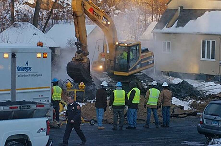A Yankee Gas crew looks over the demolition of the home on Ohio Ave Ext. which exploded last night after gas leaked into the basement of the home. One resident was injured and two excaped unharmed. Hour photo / Erik Trautmann