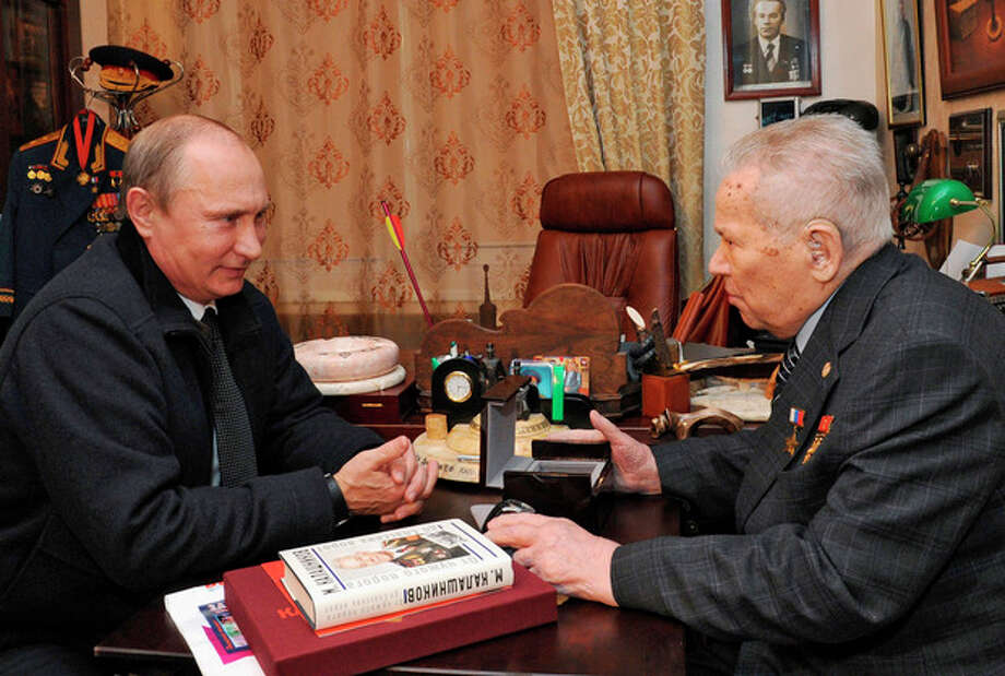 FILE - In this Wednesday, Sept. 18, 2013 file photo, Russian President Vladimir Putin, left, speaks with weapons designer Mikhail Kalashnikov, who invented the AK-47 assault rifle, in the central Russian city of Izhevsk, about 1000 kilometers (625 miles) east of Moscow. Mikhail Kalashnikov, whose work as a weapons designer for the Soviet Union is immortalized in the name of the world's most popular firearm, has died at the age of 94, Monday Dec. 23, 2013. (AP Photo/RIA-Novosti, Mikhail Klimentyev, Presidential Press Service, File) / RIA Novosti Kremlin
