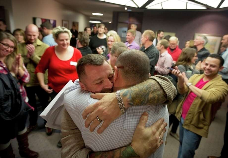 Chris Serrano, left, and Clifton Webb embrace after being married, as people wait in line to get licenses outside of the marriage division of the Salt Lake County Clerk's Office in Salt Lake City, Friday, Dec. 20, 2013. A federal judge ruled on Friday that Utah's ban on same-sex marriage is unconstitutional. (AP Photo/Kim Raff) / FR159054 AP