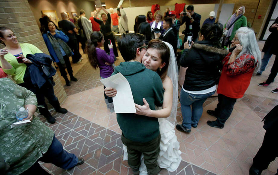 Jax and Heather Collins hug after getting married at the Salt Lake County clerk's office Monday, Dec 23, 2013. A federal judge said he will allow gay marriage in Utah to continue, denying a request from the state to halt same-sex weddings until the appeals process plays out. (AP Photo/Deseret News, Ravell Call) / Deseret News