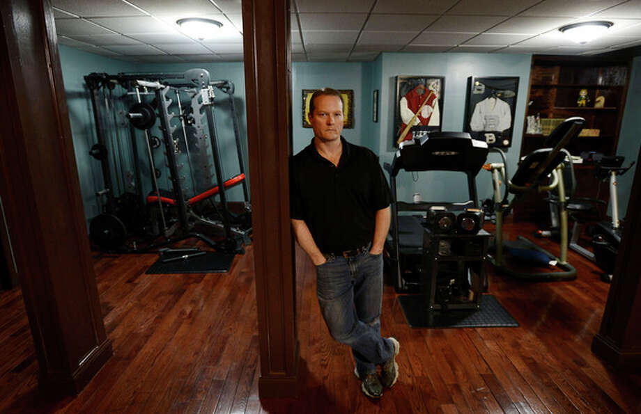 In this Dec. 17, 2013 photo, Dr. Jason Cabler poses in the exercise room of his home in Hendersonville, Tenn. Cabler, 46, suffered a heart attack on Christmas Day in 2012 while lifting weights in the basement gym. Studies indicate that heart troubles, including fatal heart attacks, spike this time of year, especially on Christmas and New Year's. (AP Photo/Mark Zaleski) / FR170793 AP
