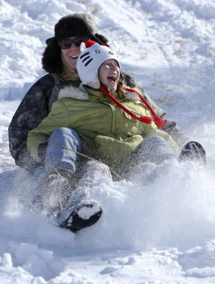 Katie Gray and her daughter Avey Gray, 10, enjoy a sled ride down the hill at the Avenue A and K-61 overpass on Sunday, Dec. 22, 2013, in Hutchinson, Kan. (AP Photo/The Hutchinson News, Lindsey Bauman)