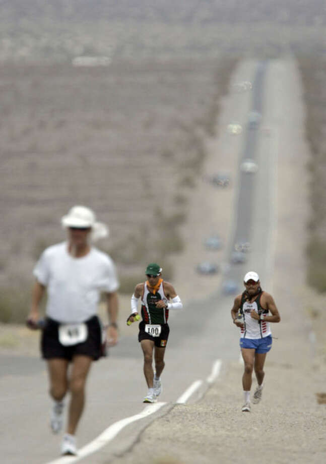 FILE - In this July 23, 2007 file photo, Jorge Pacheco, center, of Mexico, runs in Kiehl's Badwater Ultramarathon in Death Valley, Calif. The race start line wa at Badwater, Death Valley, which marks the lowest elevation in the Western Hemisphere at 280 feetbelow sea level. The race finished after 135 miles at the Mount Whitney Portals at 8,360 feet. Death Valley National Park is putting the brakes on ultramarathons and other extreme sports events that involve running and cycling until rangers can determine how safe it is to hold those competitions in a place that records the hottest temperatures on Earth. (AP Photo/Chris Carlson, File)