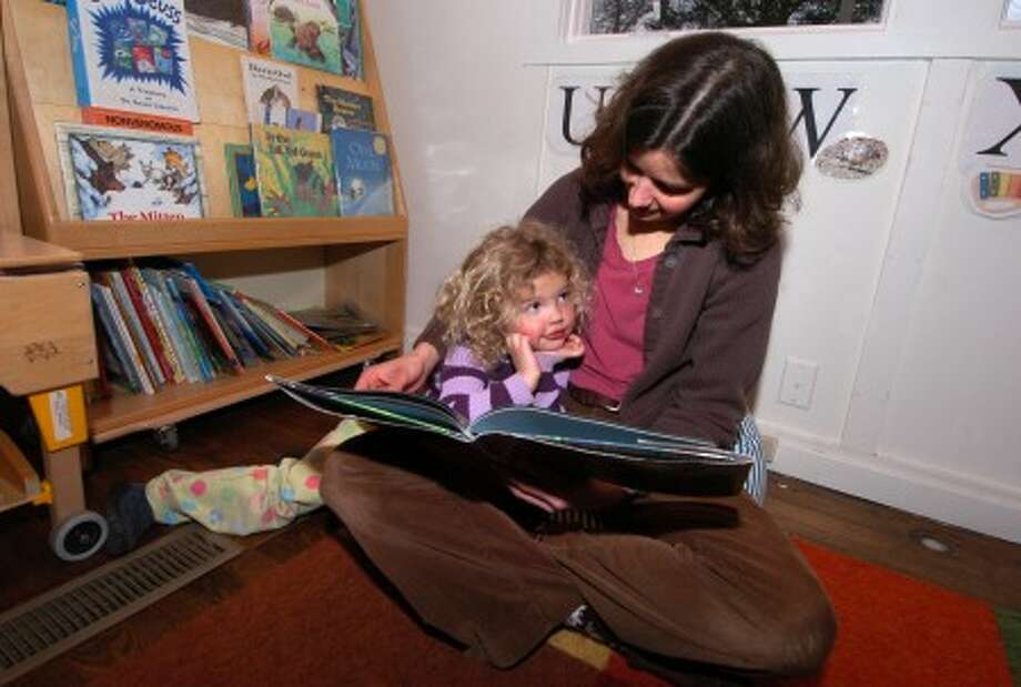 Photo/Alex von Kleydorff. Natural Worlds Preschool teacher. Amy Taylor reads to 4 yr old Anya Taylor Yeremeeva at the Woodcock Nature Center in Wilton
