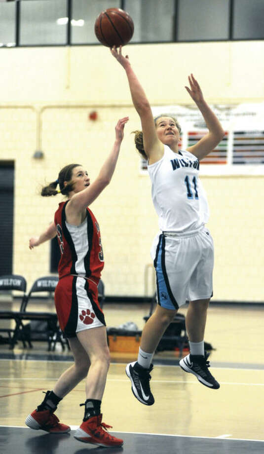 Hour photo/John NashWilton's Sara Dickinson, right, puts up a shot against the defense of Masuk's Danielle Adams during Monday's non-conference game at the Zeoli Field House. Wilton eked out a 34-33 win.