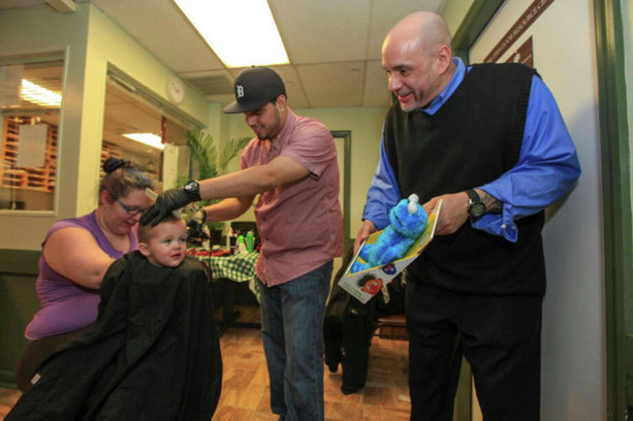 Hour photos / Chris PalermoOpen Door Shelter Manager of Program Operations Frank Concepcion offers a Cookie Monster plush toy to David Birchfield as he receives his complimentary haircut from Joel Figueroa of Joel's Barber Lounge at the emergency shelter Monday. / © 2013 Hour Newspapers All Rights Reserved.