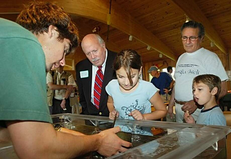 Sherwood Island Nature Center naturalist Alan Berman displays horshoe crabs for Westport first selectman Gordon Joseloff, State Represenative Joe Mioli and his grandchildren durinmg the grand opening of the center Wednesday in Westport. Hour photo / Erik Trautmann