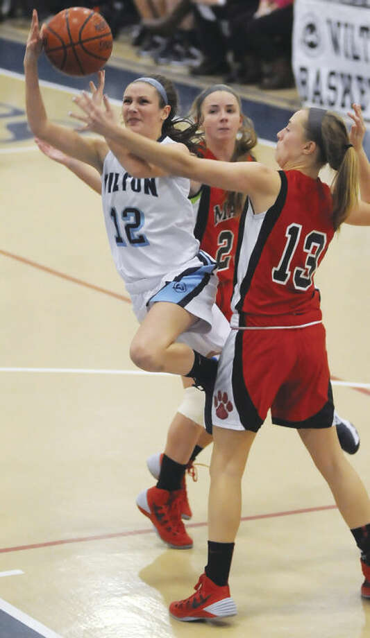 Haley Englishof Wilton, center, cuts between Masuk defenders Paige Santee (13) and Jamie Madden (rear) during Monday's non-conference game at the Zeoli Field House in Wilton. The host Warriors remained unbeaten with a 34-33 victory.Hour photo/John Nash