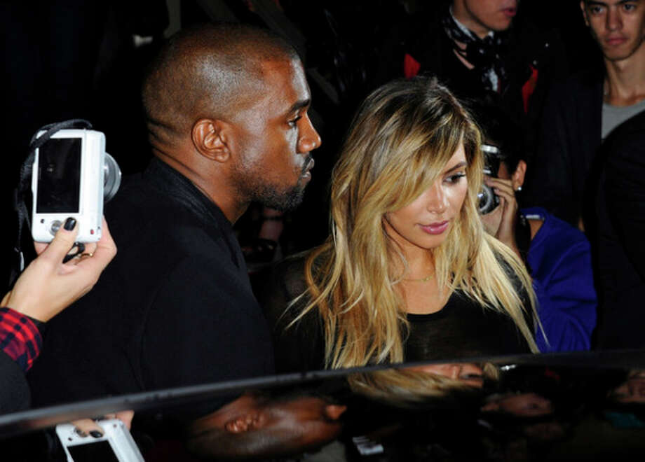 FILE - In this Sept. 29, 2013 file photo, Kanye West, left, and Kim Kardashian leave after attending Givenchy's ready-to-wear Spring/Summer 2014 fashion collection in Paris. (AP Photo/Zacharie Scheurer, File) / AP