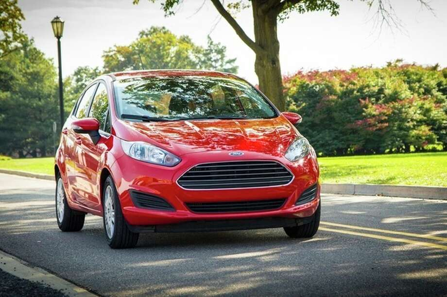 This undated photo provided by the Ford Motor Company shows the 2014 Ford Fiesta. Ford's smallest car in the United States, the Fiesta has a top fuel mileage rating from the federal government of 32 miles per gallon in city driving and 45 mpg on the highway. This combined 37-mpg mileage is for a Fiesta that's fitted with a 1-liter, three-cylinder, turbocharged, gasoline engine that generates 123 horsepower. (AP Photo/Ford Motor Company) / Ford Motor Company
