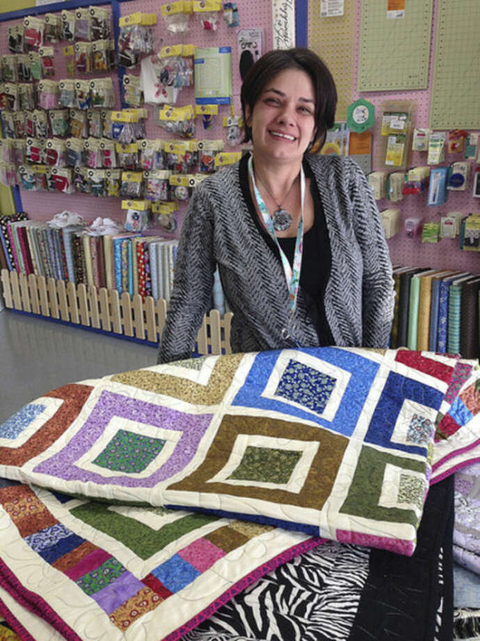 Hour photo/Chris Bosak Christie Ruiz of Christie's Quilting Boutique displays some of her quilt blankets at her Main Street store.