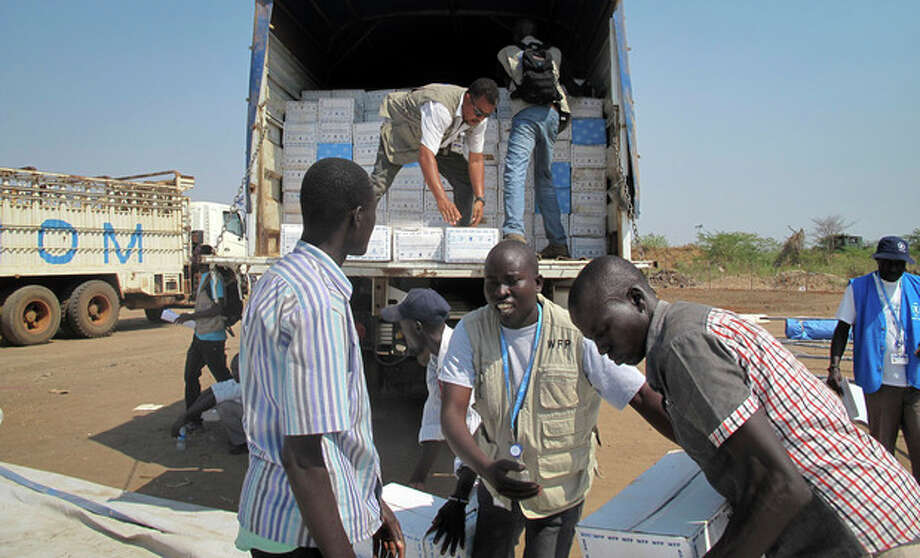 In this photo released by the World Food Programme (WFP), WFP staff and helpers unload a truck of cereal food assistance at a U.N. compound where many displaced have taken shelter in Juba, South Sudan, Tuesday, Dec. 24, 2013. South Sudan's military spokesman says there is increasing tension at a United Nations camp in the rebel-held city of Bor because armed elements have entered the congested area where the U.N. says about 17,000 civilians are seeking protection. (AP Photo/WFP, George Fominyen) / World Food Programme