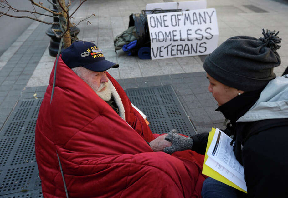 In this Wednesday, Nov. 20, 2013 photo, homeless Korean War veteran Thomas Moore, 79, left, speaks with Boston Health Care for the Homeless street team outreach coordinator Romeena Lee on a sidewalk in Boston. Moore, who said he accidentally killed his best friend with a phosphorous grenade during one firefight and spent months afterward at Walter Reed Army Medical Center in Washington, also said he has no interest in getting a government-subsidized apartment. (AP Photo/Steven Senne) / AP