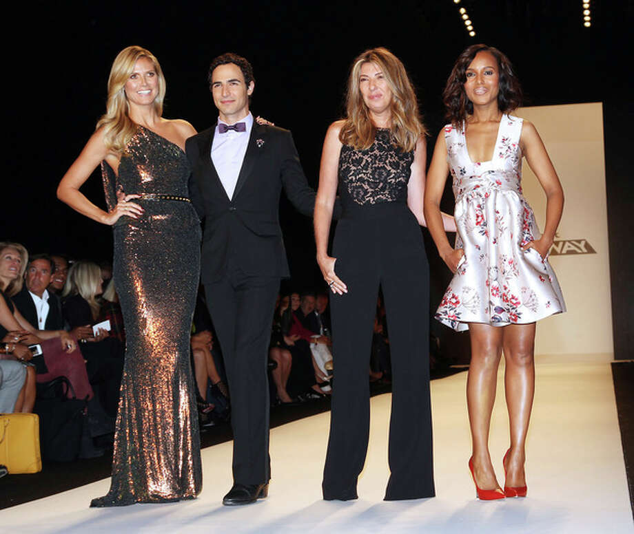 "FILE - This Sept. 6, 2013 file image released by Starpix shows, from left, host Heidi Klum, designer Zac Posen, Nina Garcia and actress Kerry Washington wearing a Stella McCartney floral frock and red leather pumps as a judge, at the ""Project Runway"" show during Fashion Week in New York. An ""it"" girl of the Hollywood-fashion nexus becomes even hotter. TV's ""Scandal"" actress Kerry Washington made glamorous appearances at New York Fashion Week, where she judged ""Project Runway"" in a pretty Stella McCartney floral number, and at the Emmys, in an eye-catching Marchesa gown. (AP Photo/Starpix, Kristina Bumphrey) / StarPix"
