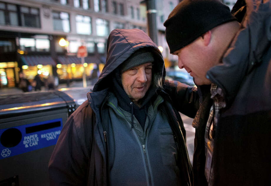AP Photo/Steven SenneIn this Thursday, Nov. 21, photo, former homeless U.S. Navy veteran Wayne Tillman, 65, left, speaks with Massachusetts Department of Veterans Services outreach team leader Christopher Doyle, in Boston. No longer homeless due in part to government vouchers that subsidize his housing, Tillman still prefers spending much of his time on the street in front of a train station where he was once homeless. / AP