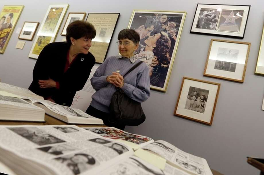 """In this photo made on Friday, Dec. 20, 2013, Indiana County tourist bureau executive director Denise Liggett, left, and Jimmy Stewart Museum board of directors president Pauline Simms look over books of photos and stories of the life of Hollywood legend Jimmy Stewart at the Jimmy Stewart Museum in Indiana, Pa. The museum dedicated to the life of the star of many films including the holiday favorite """"It's A Wonderful Life"""" is located in the off-the-beaten track town where Stewart grew up. The museum still attracts visitors from all over the country. It's full of displays not just about Hollywood, but about Stewart's service as a bomber pilot in World War II, his well-to-do ancestors, and his family life. (AP Photo/Keith Srakocic) / AP"""
