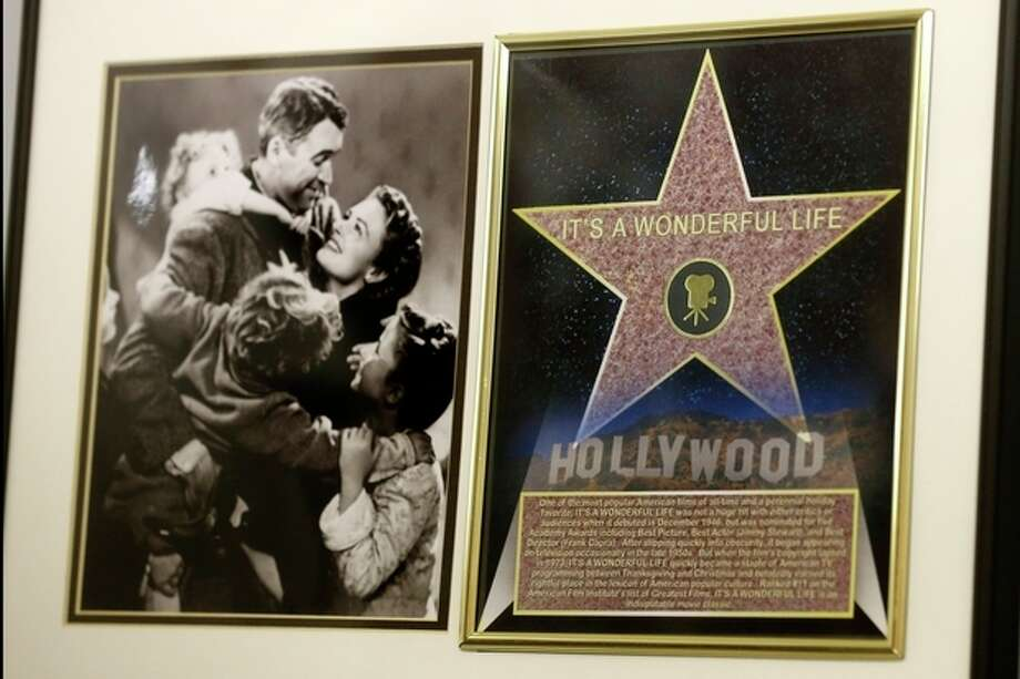 """In this photo made on Friday, Dec. 20, 2013, a framed plaque with a photograph of a scene from the 1946 film """"It's A Wonderful Life"""" starring Jimmy Stewart, left, and a Hollywood star are on display at the Jimmy Stewart Museum in Indiana, Pa. The museum dedicated to the life of the star of many films including the holiday favorite """"It's A Wonderful Life"""" is located in the off-the-beaten track town where Stewart grew up. The museum still attracts visitors from all over the country. It's full of displays not just about Hollywood, but about Stewart's service as a bomber pilot in World War II, his well-to-do ancestors, and his family life. (AP Photo/Keith Srakocic) / AP"""