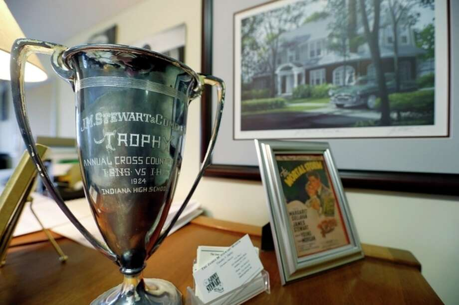 In this photo made on Friday, Dec. 20, 2013, a trophy that was awarded by the hardware store that the father of Hollywood legend Jimmy Stewart owned, sits on the desk of Timothy Harley, executive director of the Jimmy Stewart Museum, in front of a portrait of the house where Stewart grew up, in Indiana, Pa. (AP Photo/Keith Srakocic) / AP