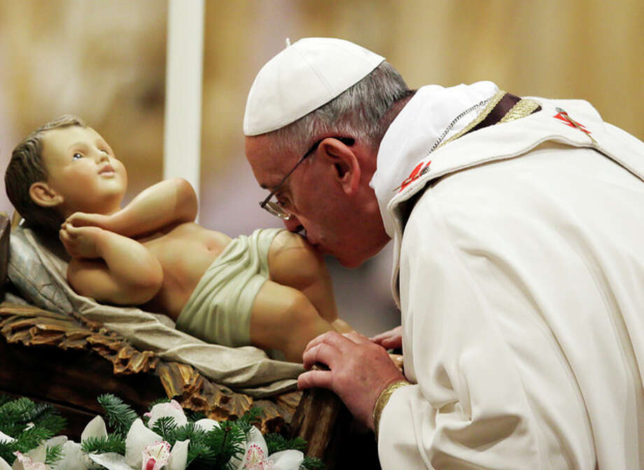 Pope Francis kisses a statue of baby Jesus as he celebrates the Christmas Eve Mass in St. Peter's Basilica at the Vatican, Tuesday, Dec. 24, 2013. (AP Photo/Gregorio Borgia) / AP