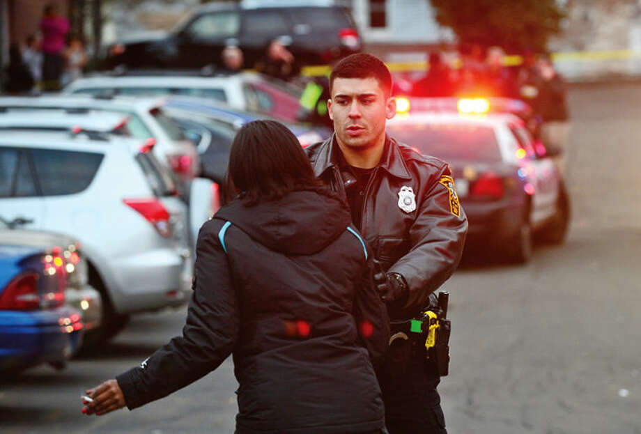Hour photo / Erik Trautmann Norwalk police hold back residents after a shooting at Monterey Village Tuesday evening.