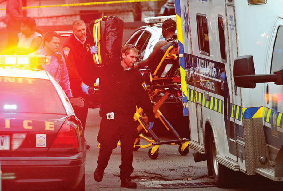 Hour photo / Erik Trautmann Paramedics evacuate a shooting victim as Norwalk police investigate the incident at Monterey Village Tuesday evening.