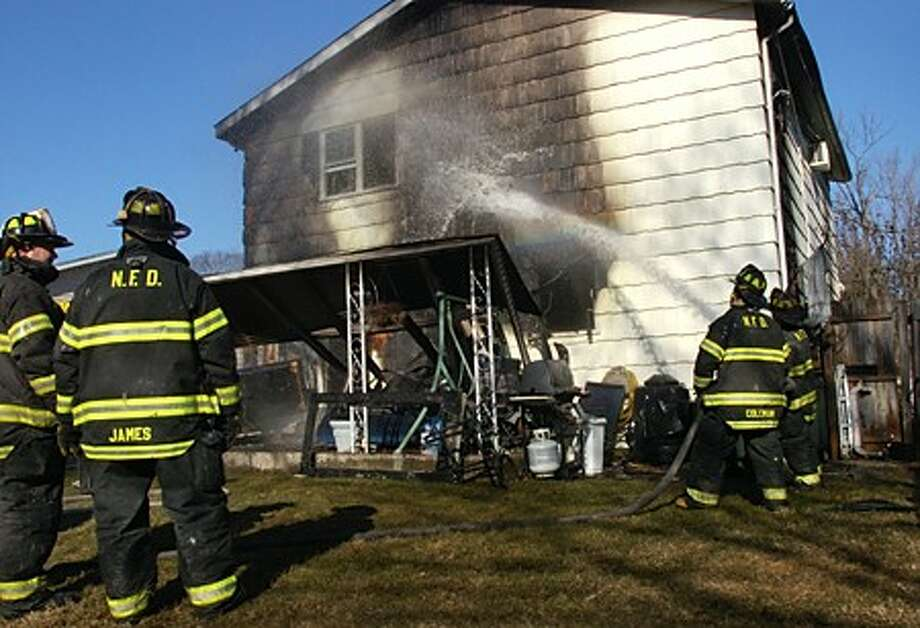 Norwalk firefighters douse a home at 364 Flax Hill Rd. that was gutted by fire Tuesday morning. Hour photo / Erik Trautmann